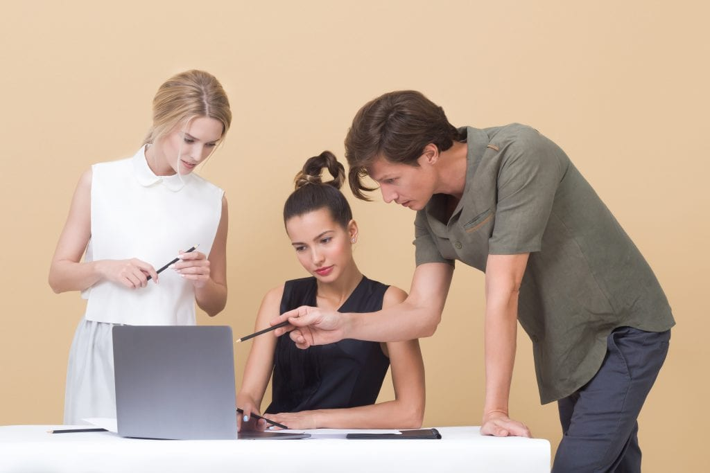 two women and a man looking at a computer