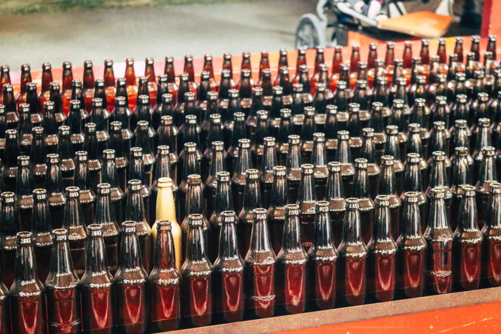 a series of bottles with one standing out from the rest of the pack to show how to stand out to win business