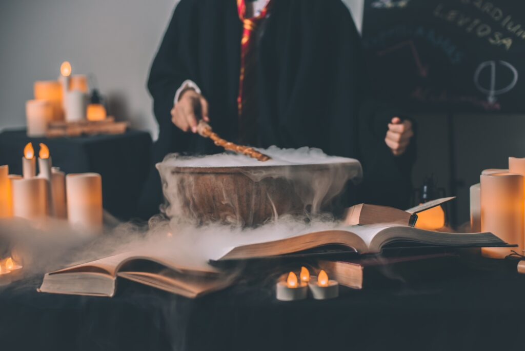 a person holding a wand in front of a cauldron with candles and books