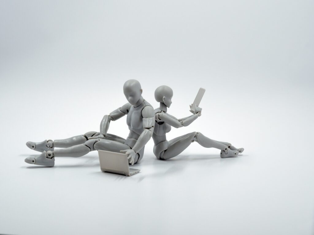 two toy robots sitting back to back using computers