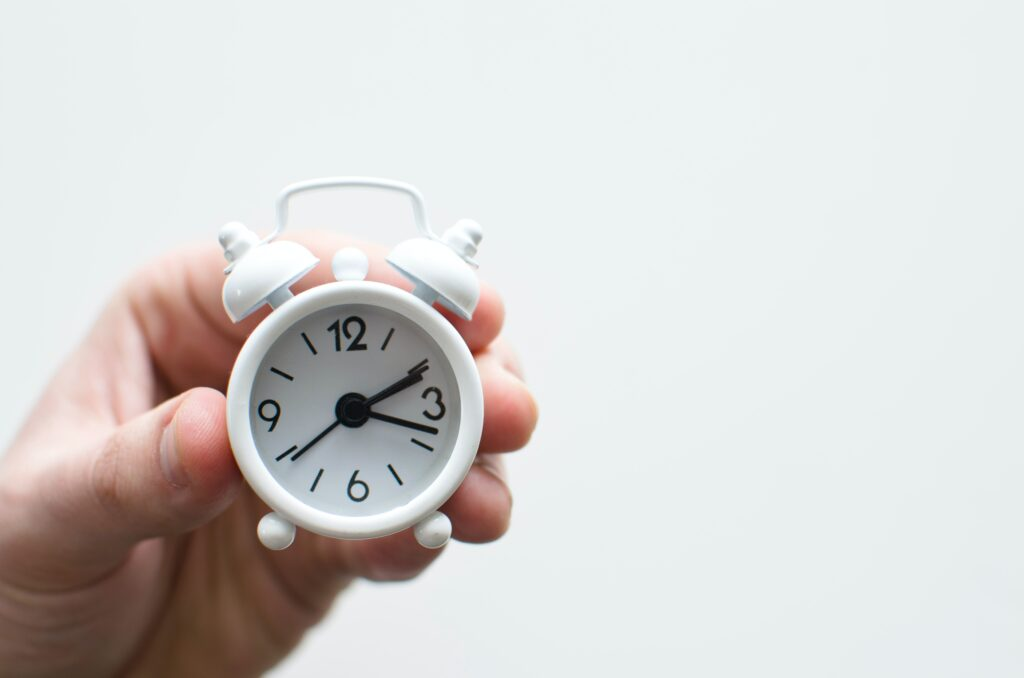 hand holding a clock to show proposal management deadlines